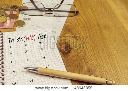 To do list on a spiral notebook - Graphic notebook with a to do list placed on a wooden office desk surrounded by bills money and a pair of glasses