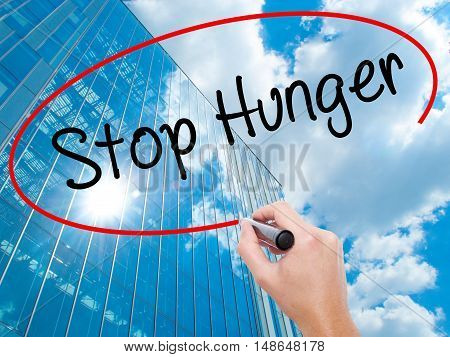 Man Hand Writing  Stop Hunger With Black Marker On Visual Screen