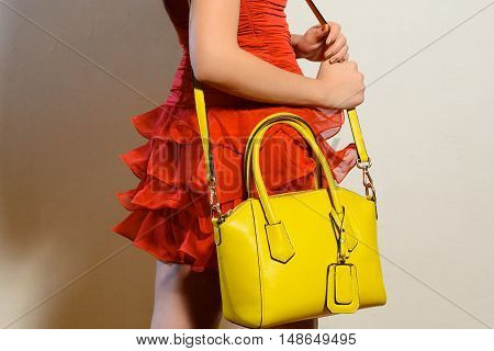Fashionable young woman in a red dress with yellow handbag over your shoulder