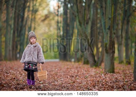 Little funny girl throws autumn leaves in the park on sunny fall day