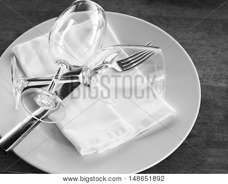 Two glasses on a plate with cutlery