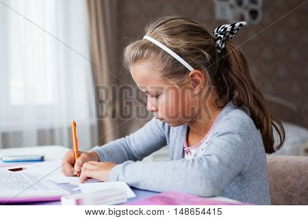 Serious little school girl doing homework sitting with a pencil at the table