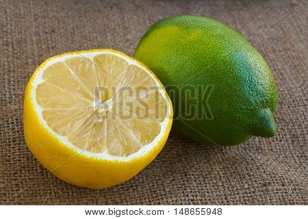 Fresh green and white lemons. One is cut into half.