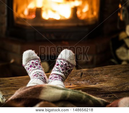 Warming and relaxing near fireplace. Child feet in front of fire.