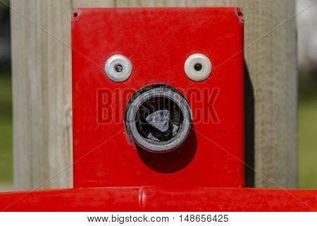 Bolts and screws forming a face on a red plate