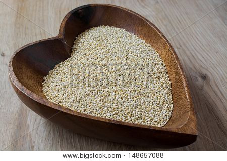 grain of a quinoa in a wooden bowl in the form of heart