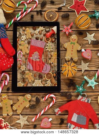 laptop and a variety of Christmas decorations on brown background