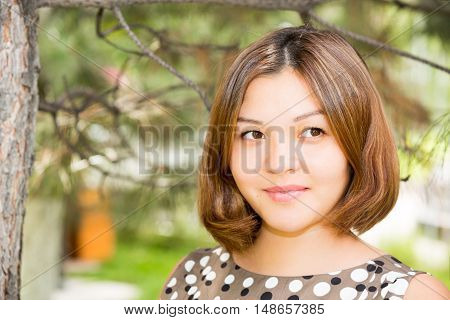Portrait of the asian Kazakh young beautiful smiling woman outdoor