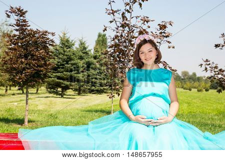 Happy pregnant woman with big belly rest on nature