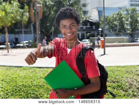 Latin american student with dental braces showing thumb outdoor in the city in the summer