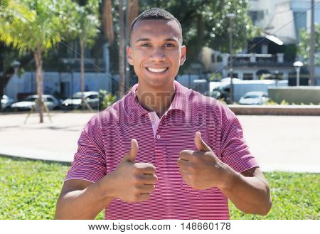 Mexican guy in the city showing both thumbs outdoor in the summer