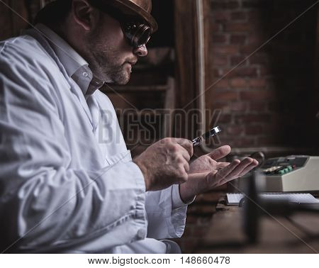 Vintage businessman investigating by office desk with magnifying glass
