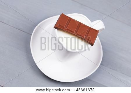 Bar of milk chocolate on a white cup of milk on grey natural wood background. Concept of making hot drink for autumn fall season.