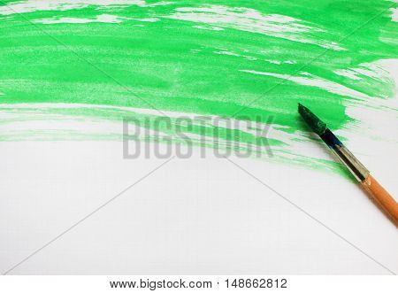 Painted abstract watercolor splash light bright colorful green grunge wet paper texture pattern with paintbrush. Simple background painting art design creative leisure concept close up with copy space