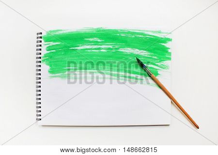 Painted abstract watercolor splash light bright colorful green grunge wet paper pattern on notebook page with paintbrush isolated on white table. Textured vintage simple empty dirty background. Painting art creative leisure concept