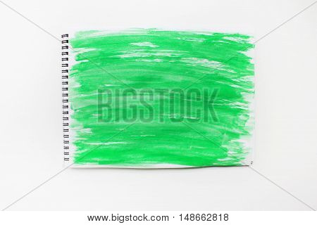 Painted abstract watercolor splash light bright colorful green grunge wet paper pattern on notebook page isolated on white table. Textured vintage simple empty dirty background