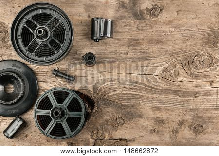 35 mm photo film and container for film development lying on wooden floor top view
