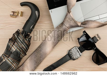 Fashion and business notebook wristwatch and tie on a wooden table as background top view