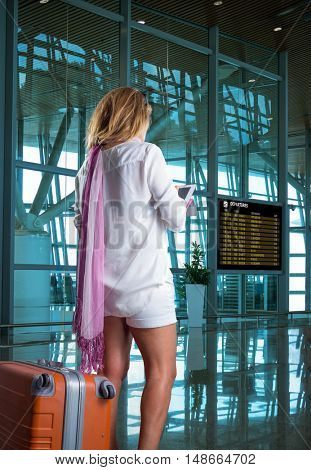 Young woman with luggage at the international airport.