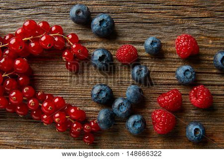 Berries mix on wooden board blueberries red currants and raspberries