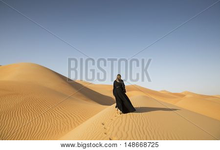 woman in traditional emirati dress (abaya) in Liwa desert