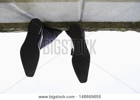 Feet dangling over wall, low angle view