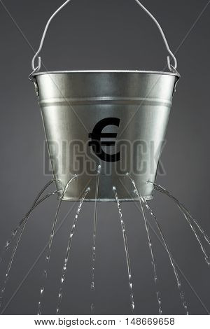 Water leaking from bucket with euro symbol