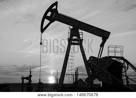 Oil rig silhouette during sunset in the oilfield. Oil and gas concept. Black and white.