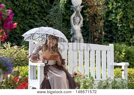 Girl Sitting On A White Bench With A Book