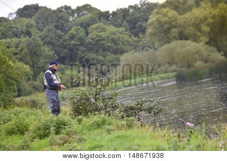 Fly-fisherman fishing in river from riverbanks