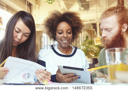 International Team Work. Three People Working Together At Cafe: Asian Woman Studying Financial Repor