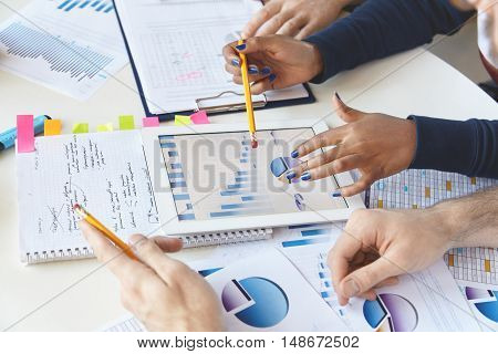 Colleagues Working Together On Financial Report Using Modern Gadget. African Girl With Pencil Presen