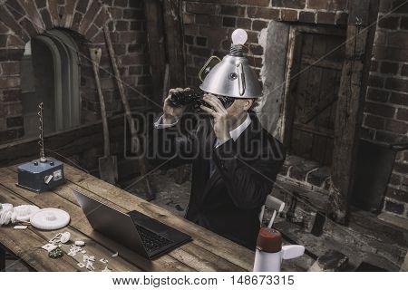 Vintage businessman sitting by office desk with binoculars