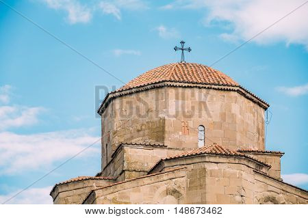 Mtskheta, Georgia. Close View Of Tiled Dome With The Cross Of Jvari Georgian Orthodox Monastery, World Heritage By Unesco. Blue Summer Spring Cloudy Sky Background.