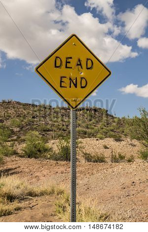 Dead End Road Sign With Bullet Holes And Peeling Letters In Arizona Desert