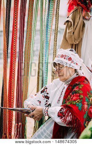 Gomel, Belarus - September 12, 2015: Woman in national Belarusian folk costume weaving belt