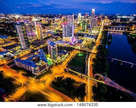 Night time Cityscape of the Texas Capital City of Austin TX with Colorful city lights and bridges crossing the colorado river and Frost Bank tower lit up bright