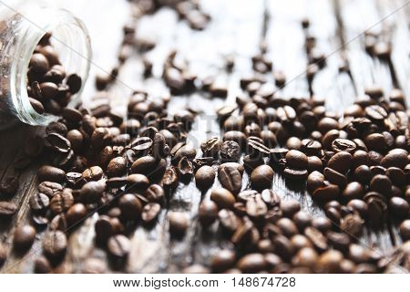 Coffee beans are on the wooden textured table with the glass jar