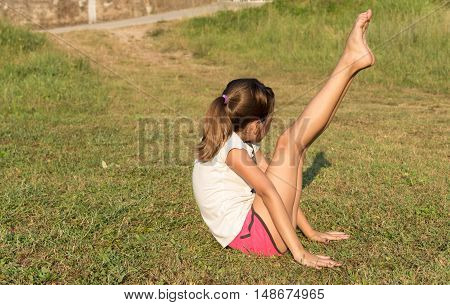 The young girl engaged in yoga gymnastics on the grass. Healthy lifestyle.