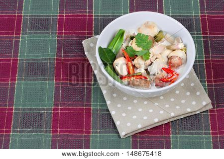 Chicken and galangal in coconut milk soup is popular Thai cuisine season with mixed herb as galangal,mushroom,cabbage,kaffir lime leaves,chili,carrot,red onion,hot basil and meat to spicy sour soup.