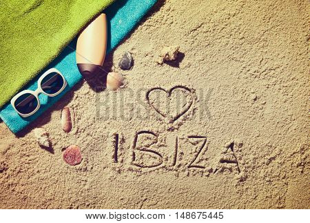 Top view of sandy beach with summer accessories and love sing and Ibiza text