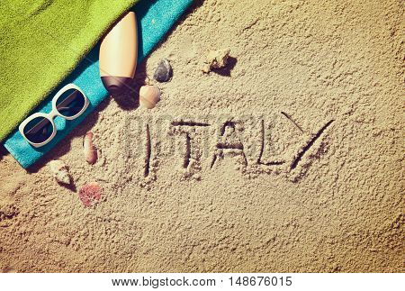 Top view of sandy beach with summer accessories and Italy text