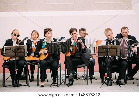 Gomel, Belarus - September 12, 2015: People from city string band Orchestra playing music on street