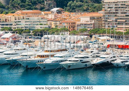 White Yachts Of Different Sizes Are Moored At City Pier, Jetty In Sunny Summer Day in Monte Carlo, Monaco