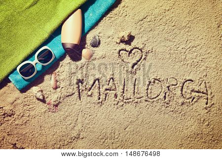 Top view of sandy beach with summer accessories and love sing and Mallorca text