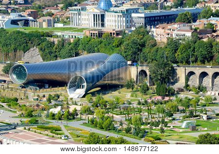 26.08.2016 Tbilisi, Georgia. aerial view on Tbilisi downtown rike park, modern city hall building and river Mtkvari