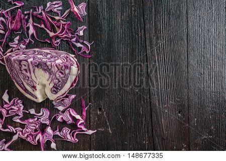 Red cabbage, sliced and chopped on the dark wooden surface