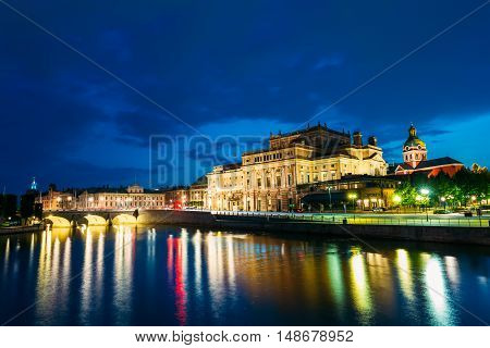 Stockholm, Sweden. The Scenic Night View Of Illuminated Royal Swedish Opera Theatre And Norrbro Arch Bridge Over Norrstrom Waterway With Lights Reflections In The Water Under Dramatic Blue Sky.