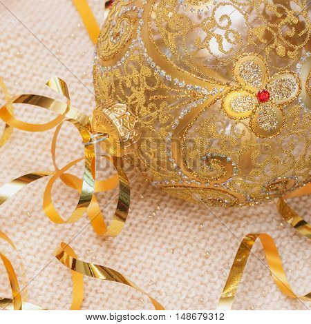 Golden Christmas ball with ribbons decoration glass ball on a light knitted scarf, Christmas and New Year's concept. With place for your text. Square