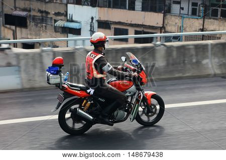 BANGKOK, THAILAND - DECEMBER 23: An unidentified traffic police officer rides a motorbike on a city street on December 23, 2013 in Bangkok, Thailand.